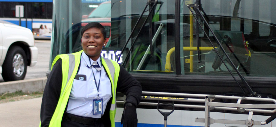 Bus operator in front of bus, smiling and ready to work.