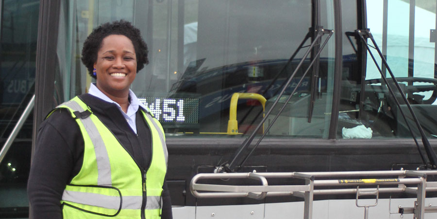 Bus driver in front of bus, smiling and wearing a safety vest.